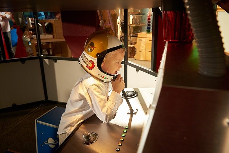 Boy using space shuttle in Discovery Room.
